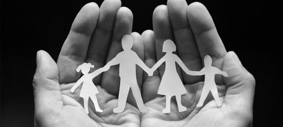Hände die eine Papierfigurenfamilie als Symbol für Familienrecht halten